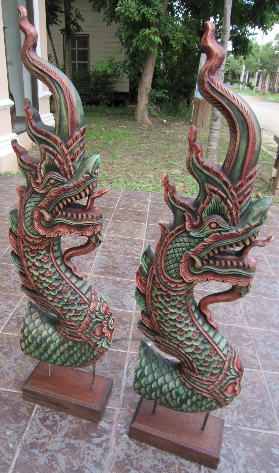 Pair of large hand carved naga heads with stand